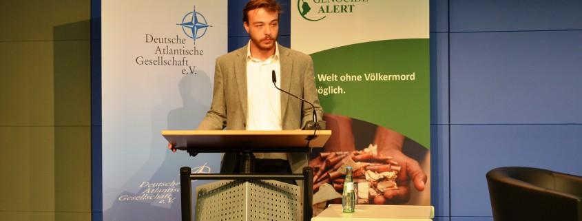"""Gregor Hofmann, stellvertretender Vorsitzender von Genocide Alert begrüßt die Besucher zur Diskussion """"Zwanzig Jahre Srebrenica - Folgen und Lehren für die internationale Staatengemeinschaft""""; Quelle: eigenes Foto."""