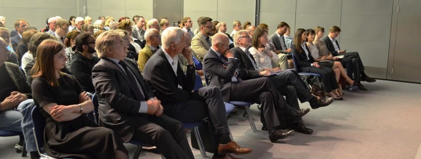 Zu Beginn der Veranstaltung verfolgen die Diskutanten und das Publikum die Keynote-Speech von Außenminister a.D. Klaus Kinkel; Quelle eigenes Foto.
