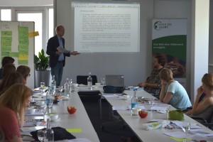 Sebastian Gräfe erläutert in Berlin anhand des Südsudans Praxis und Schwierigkeiten von UN Friedensmissionen beim Schutz von Zivilisten; Quelle: Genocide Alert