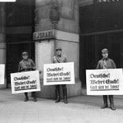 "Israel's Department Store in Berlin on April 1, 1933 at the start of the Nazi boycott of Jewish-owned businesses. These are members of the SA (Sturmabteilung) holding placards that say: ""Germans defend yourselves! Don't buy from Jews."" (Source: Wikimedia Commons/Bundesarchiv Bild 102-14469)"